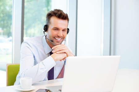 Szczęśliwy konsultant z zestawem słuchawkowym, patrząc na laptopa