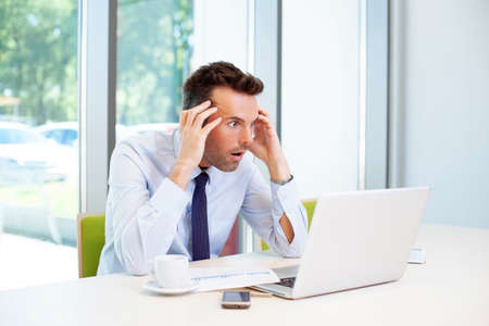 horrified: Horrified businessman working in office on laptop