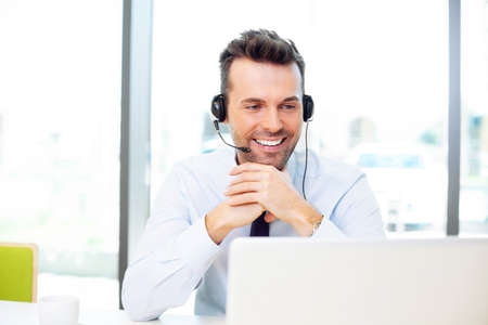 Happy businessman talking with headset