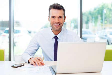 using the computer: Feliz hombre de negocios que trabaja en la oficina en la computadora portátil. Foto de archivo