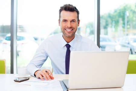 Happy businessman working at the office on laptop.