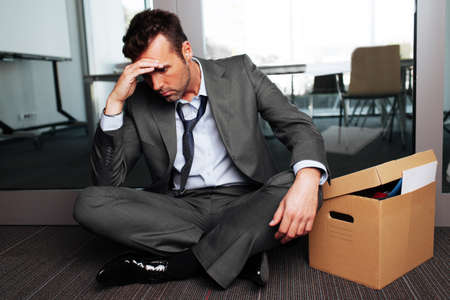 unemployed dismissed: Sad fired businessman sitting outside meeting room after being dismissed