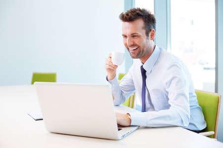 랩톱에서 입력하는 동안 사무실에서 커피를 마시는 잘 생긴 남자