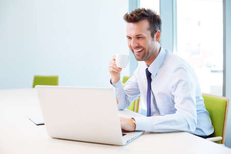 Handsome man drinking coffee in office while typing on laptop