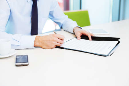 write a letter: Signing contract. Business concept. Closeup of businessman working in the office. Stock Photo