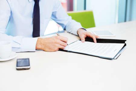 schreiben: Unterzeichnung des Vertrags. Geschäftskonzept. Nahaufnahme der Geschäftsmann im Büro arbeiten.