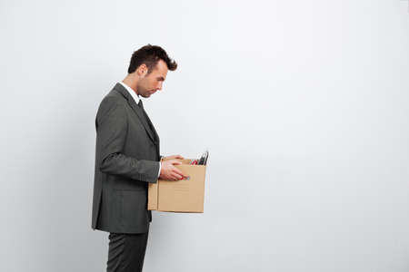 unemployed dismissed: Dismissed businessman carrying box. Isolated