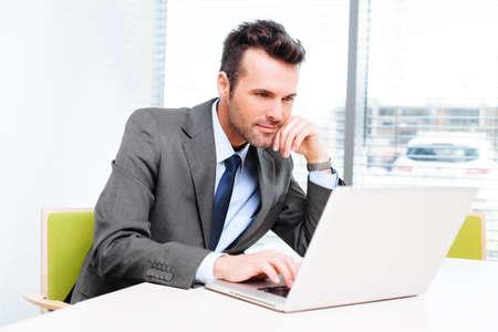 オフィスの彼のラップトップに取り組んで忙しいサラリーマンは。