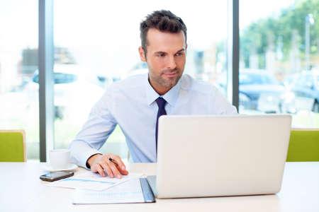 empleado de oficina: Hombre que trabaja en la oficina en la computadora port�til Foto de archivo