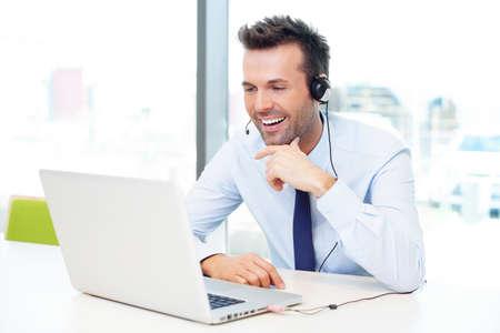 Geschäftsmann mit einem Headset im Gespräch mit seinem Laptop