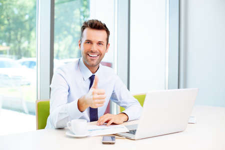 Businessman showing thumbs up in the office Foto de archivo