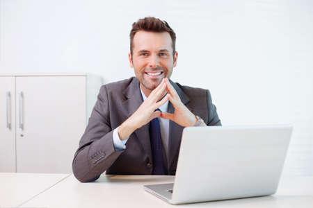 机に座っている自信の実業家 写真素材