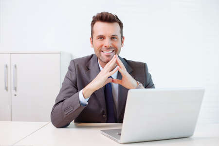 Confident businessman sitting at the desk