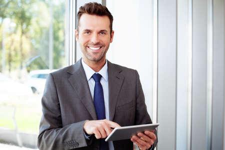 オフィスでラップトップに立って幸せの実業家