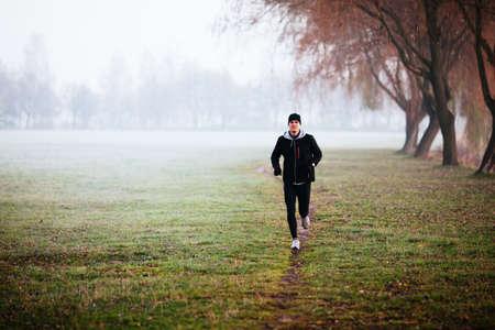 fitness hombres: Hombre que se ejecuta durante el tiempo de niebla en invierno o en otoño mañana.