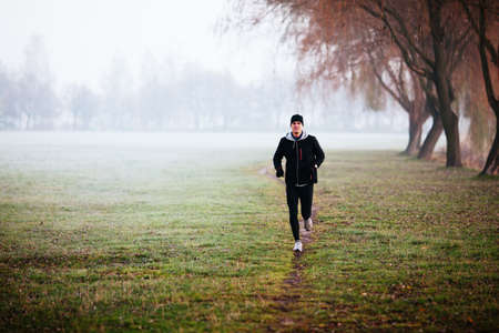 winter weather: Man running during foggy weather at winter or autumn morning.