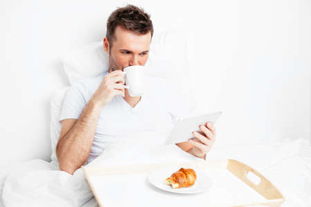 bedlinen: Portrait of a handsome man looking at a tablet and drinking coffee