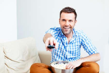 hombre feliz hermoso que sostiene un mando a distancia
