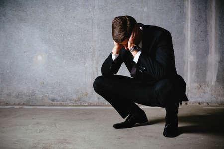 Junge Geschäftsmann hockend und suchen frustriert