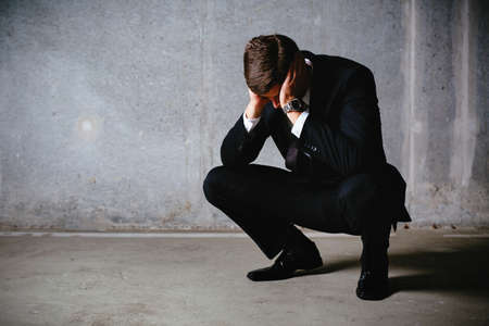 Young businessman squatting and looking frustrated