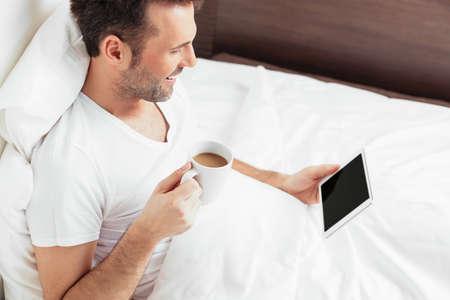 bedlinen: Handsome man browsing internet in bed Stock Photo