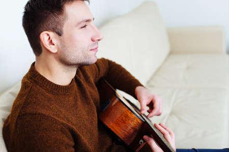 Junger Mann auf einem Sofa und spielt Gitarre sitzen photo