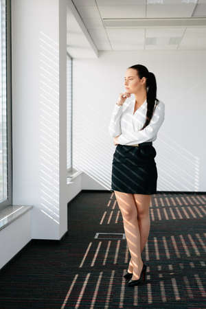 decisive: Photo of a female executive standing by a window and thinking Stock Photo