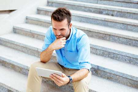 young male: Photo of a student using a tablet and revising for his exam while sitting outdoors Stock Photo