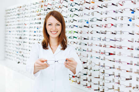 optician: Optician presenting  eyewear frames Stock Photo