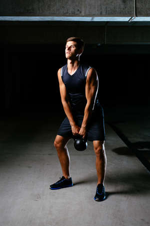 Muscular athlete working out with a kettlebell Standard-Bild