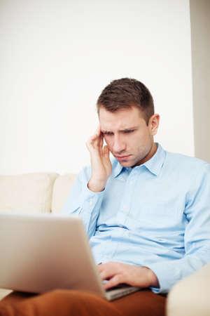 Junger Mann mit einer schmerzhaften Gesicht Blick auf einem Laptop photo