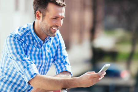 man looking: Portrait of a young handsome man holdkng a mobile