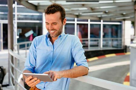 Foto von einem gut aussehend Mann im Internet surfen auf einem Tablette beim Stehen auf der Straße