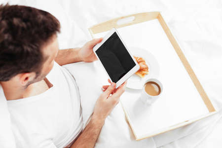 bedlinen: Man sitting in bed and holding a tablet