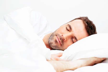 白い寝具で寝ているハンサムな若い男 写真素材