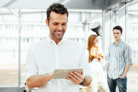 informal: Young happy professional holding a tablet