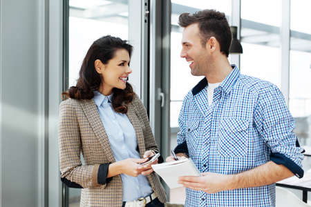witty: Young couple having a witty conversation in an office Stock Photo