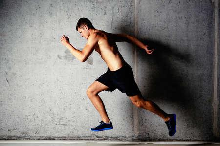 Foto eines laufenden muskulösen Sportler auf einem konkreten Hintergrund