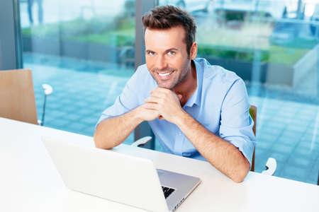 Junge lächelnd Student sitzt vor einem Laptop