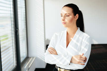 Photo of a confident female manager looking through a window Stock Photo