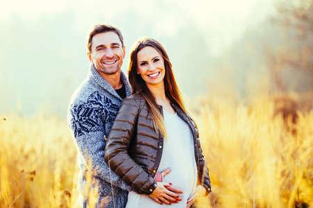 Happy pregnant couple in nature