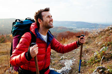 one young man: Happy man hiking with backpack during fall wearing down jacket