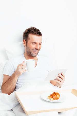 Glücklicher junger Mann im Bett mit einer Tablette und eine Tasse Kaffee Lizenzfreie Bilder
