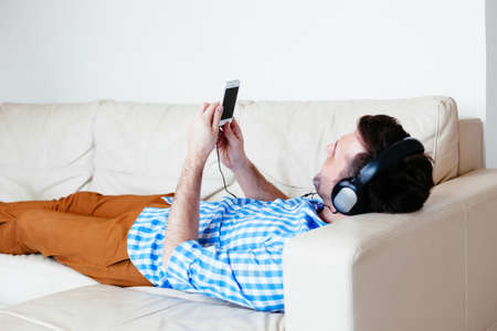 chillout: Young man with headphones lying on a sofa and listening to music