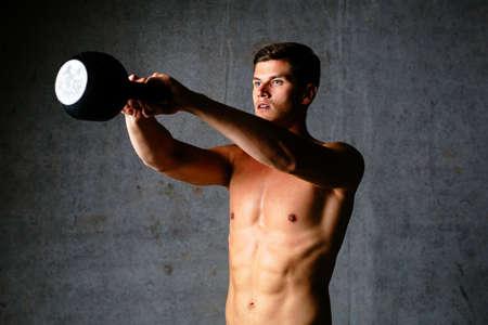 Foto eines jungen Athleten eine Pose mit einer Kettle halten
