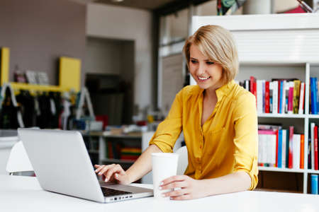 webdesigner: Happy female student  looking at her laptop