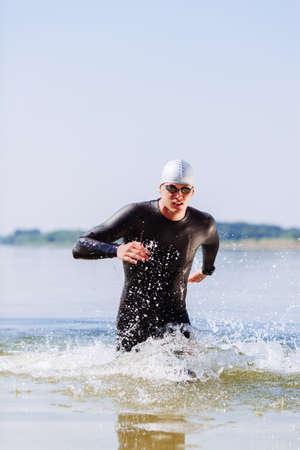 Triathlonist Aufstehen aus dem Wasser nach einem Rennen