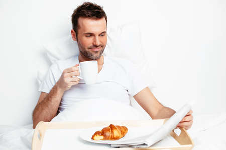 bedlinen: Portrait of a young man reading and drinking in bed Stock Photo