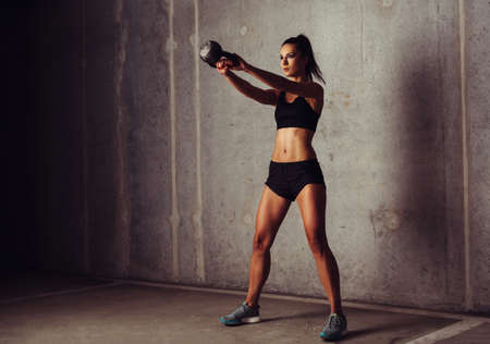 Brunette sportswoman working out her arms with a kettlebell
