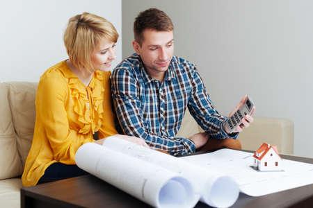 Junges Paar sitzt auf einem Sofa und den Bau Budget Berechnung